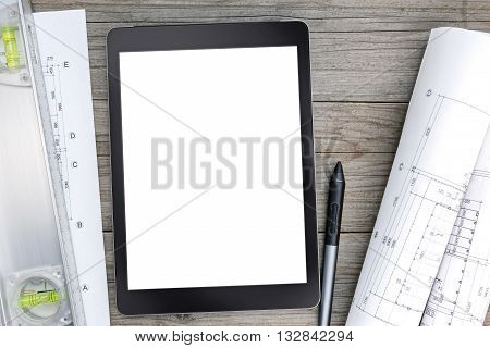 Architectural Blueprints With Spirit Level And Digital Tablet On Gray Wooden Desk