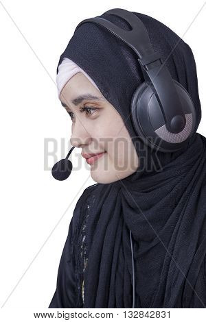 Image of female Arabian worker wearing headscarf and headphones isolated on white background