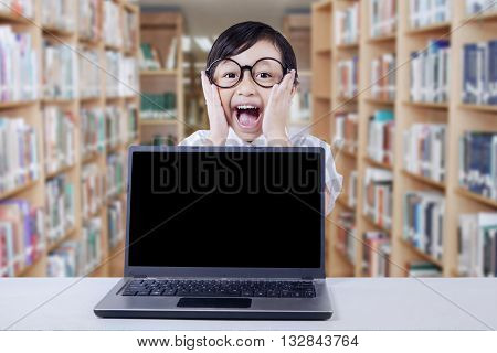 Female kindergarten student wearing glasses and yelling in the library with empty laptop screen on the table