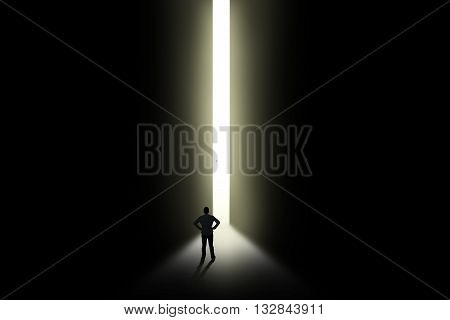 Silhouette of man entering dark room with bright light in doorway