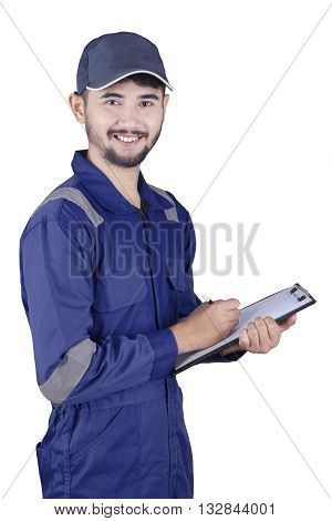 Portrait of a middle eastern mechanic standing in the studio while wearing uniform and holding a clipboard