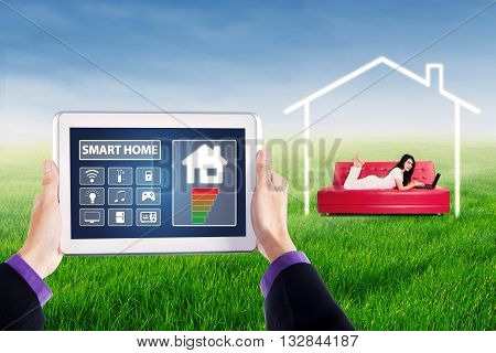 Close up of hands holding a tablet with smart house controller applications shot with young woman using laptop on sofa at field