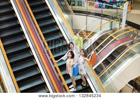 happy young woman on escalator in shopping mall