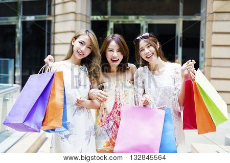young Women group Carrying Shopping Bags On Street