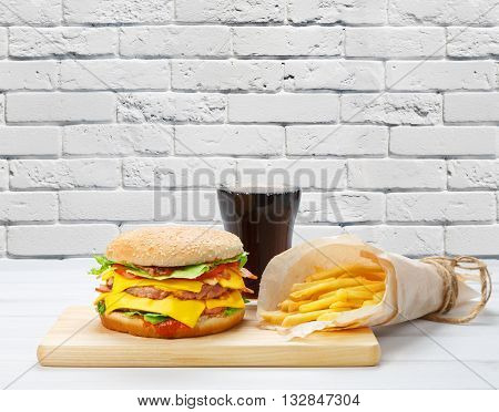 Fast food with copyspace. Hamburger, potato fries in brown wrapping paper, cola drink. Takeaway food. French fries, Cola glass, double cheeseburger or hamburger at wood and white brick wall background