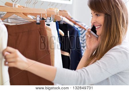 Woman using mobile phone in clothes shop
