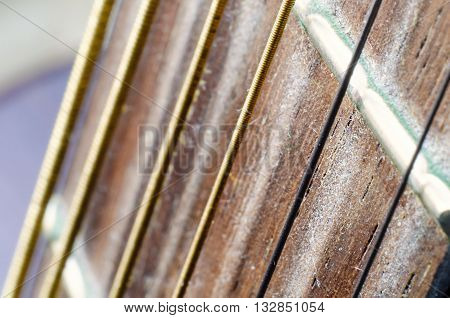 a guitar neck with metal strings macro