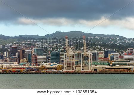 Wellington New Zealand - November 17 2014: Wellington cityscape in cloudy weather capital city of New Zealand. Timber for export cars harbor crane and container crates on wharf of Wellington Harbour in New Zealand.