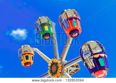 Ferris wheel of an amusement park with blue sky background