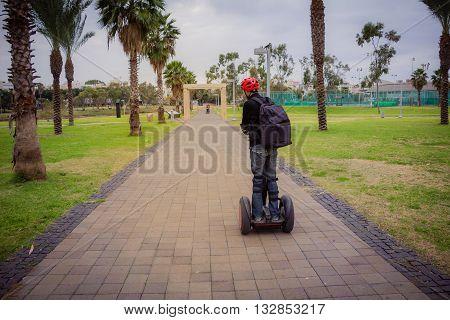 Man riding on a personal transporter device in the park.