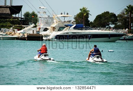 PUERTO SOTOGRANDE, SPAIN - JULY 18, 2008 - Men on jet skis in the marina Puerto Sotogrande Cadiz Province Andalucia Spain Western Europe, July 18, 2008.