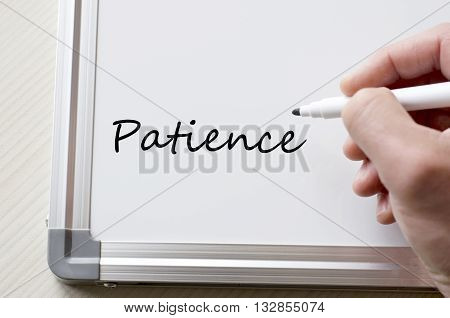 Human hand writing patience on whiteboard .