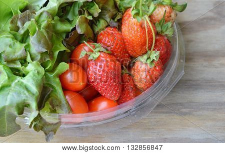 strawberry and cherry tomato with vegetable on plastic tray