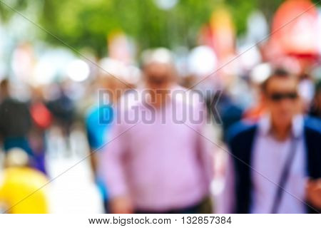 Urban street with pedestrians out of focus unrecognizable everyday people in urban environment