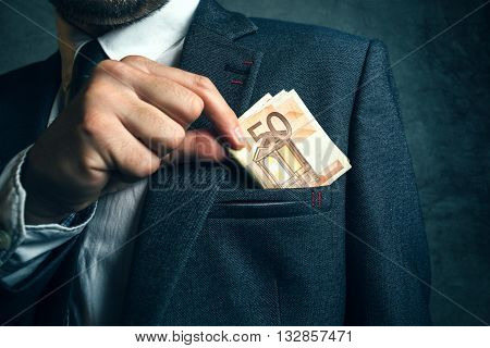 Businessman putting euro banknotes money in his suit pocket elegant businessperson with cash.