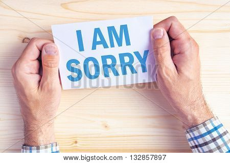 I am sorry message top view of male hands holding apologizing card