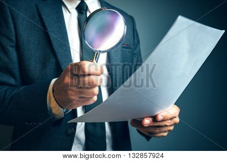 Lawyer reading legal contract agreement disclaimer with magnifying glass person in elegant business suit reading document.