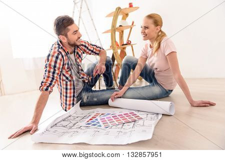 It only begining. Smiling young couple dreaming how they will furnish apartment, sittin on floor their new house and looking each other