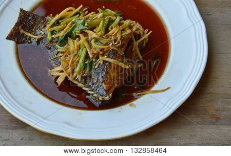 deep fried fish in ginger soy sauce on dish