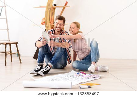 I want this color. Happy couple planning decoration when moving home sitting on floor, using laptop