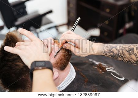 Man shaving his client with straight razor in barbershop