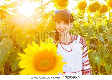 Beautiful smiling girl in national ukrainian blouse embrodery looking to camera on a sunflower field on sunset backlight