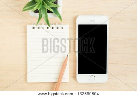 Top view of office desk table with mobile phone spiral notebook pencil and small tree in a white pot on wood table