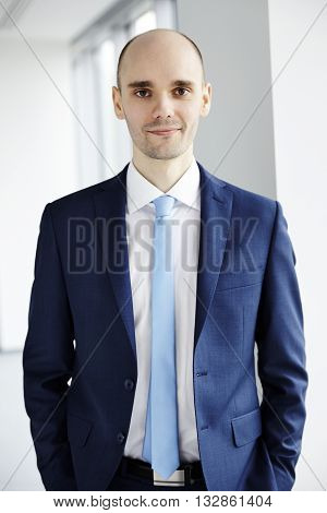 Calm young businessman standing in the office. Hands in pockets. Light background.