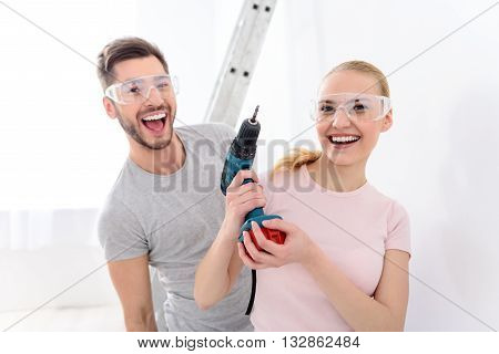 Doing repairs together. Beautiful smiling girl holding drill in her hands next to smiling guy on background of white wall and ladder in special protective glasses