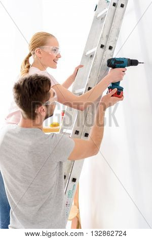 Doing hard man job. Young guy helping girl keeping drill and making hole in white wall, standing on ladder, in special protective glasses