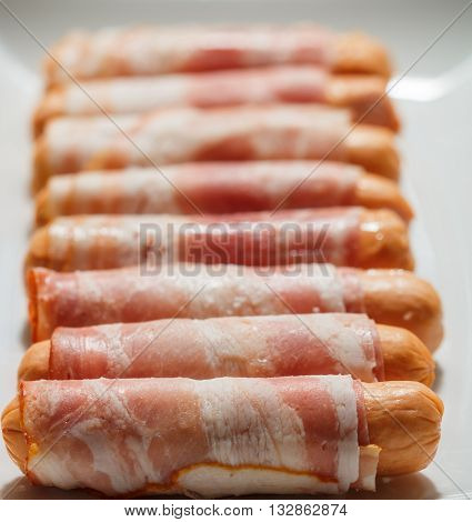 Sausages wrapped in bacon ready for roasting