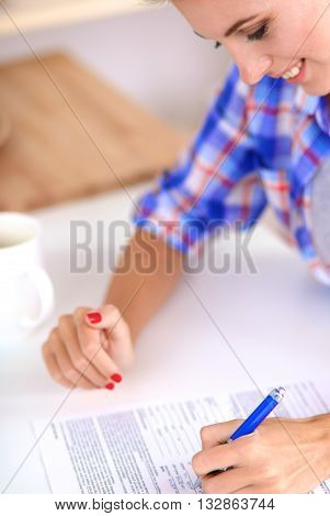 Beautiful young woman writing something in her note pad.