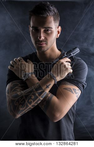 Young handsome man holding a hand gun, wearing black t-shirt, arms crossed on chest, on dark background in studio