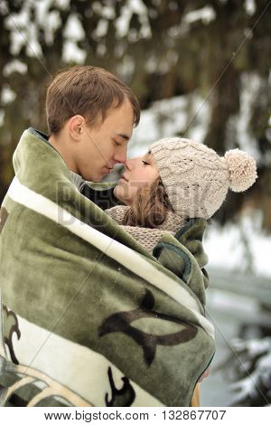 Handsome man kiss on the forehead her beloved, beautiful, pretty, attractive girl with sweater, mittens, winter, cold, snow forest, hut, love, happy, togetherness, couple, lucky, together, two, young, family, romance