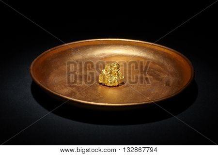 Closeup of big gold nugget in copper plate black background closeup