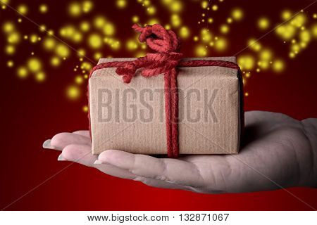 christmas gift box wrapped with a red ribbon on a female hand on red background and glitter