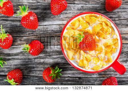 corn flakes with milk and strawberry in a red cup on an old rustic table studio lightrs close-up top view