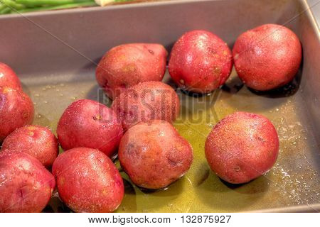 Red potatoes prepared for cooking with olive oil and salt