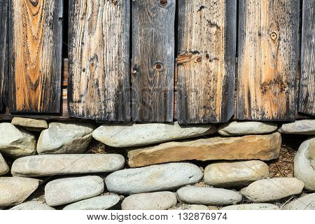 Wooden Wall and Stone Basement of Traditional Rural Bungalow with Old Rough Planks of Wood