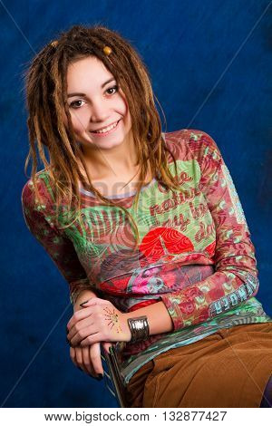 portrait of a beautiful young woman with dreadlocks against a blue background