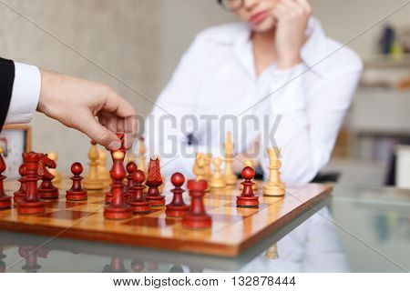 Man and woman playing chess in office. Boss moves with black king