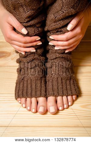 Beautiful beige pedicure and manicure. Legs in brown knitted socks on a wooden floor