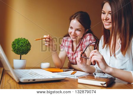 Two pretty girls in the office work in informal meeting
