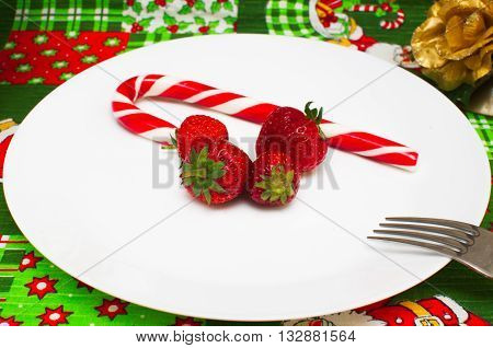 New Year Christmas Christmas tablecloth with a pattern of Santa Claus, CHRISTMAS HOLLY, gifts, a fork with a plate of fresh red berries and strawberries and candy in Christmas red and white stripes and the background color of the flower golden candlestick
