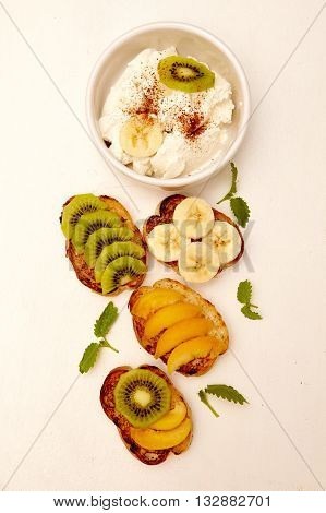 Various fruit sandwiches with banana kiwi apple apricot and ricotta. Healthy organic and vegan breakfast on white background.