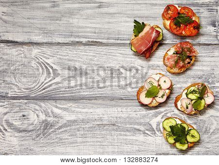 sandwiches with ricotta cucumber radishes bacon and tomatoes on a gray wooden board. Top view copy space. breakfast concept.