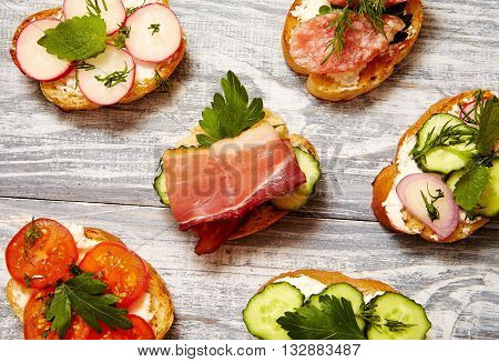 sandwiches with ricotta cucumber radishes bacon and tomatoes on a gray wooden board. breakfast concept.