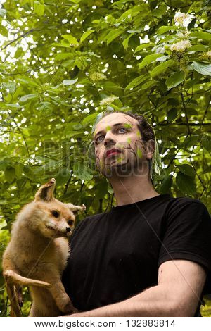 man with face paint has a fox in the arm