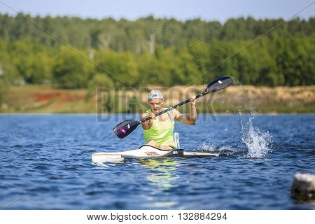 Chelyabinsk Russia - May 28 2016: athlete at rowing kayak on lake spray of water under paddle during Ural championship in rowing