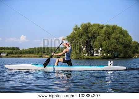 Chelyabinsk Russia - May 28 2016: muscular male athlete in a canoe rowing during Ural championship in rowing